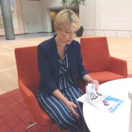 """Socialminister Annika Strandhäll sitter i en röd fåtölj och läser en tidning med rubriken """"Lös BB-krisen"""""""