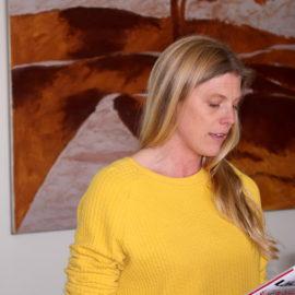 Kvinna med långt blont hår som är utsläppt och gul tröja, porträtteras. Hon läser från ett papper i sin hand.
