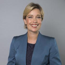 Socialförsäkringsminister Annika Strandhäll i ett porträtt där hon ler och ser rakt in i kameran. Hon har en blå kavaj på sig med en mörkblå topp under. Hennes hår är blont och kortklippt.