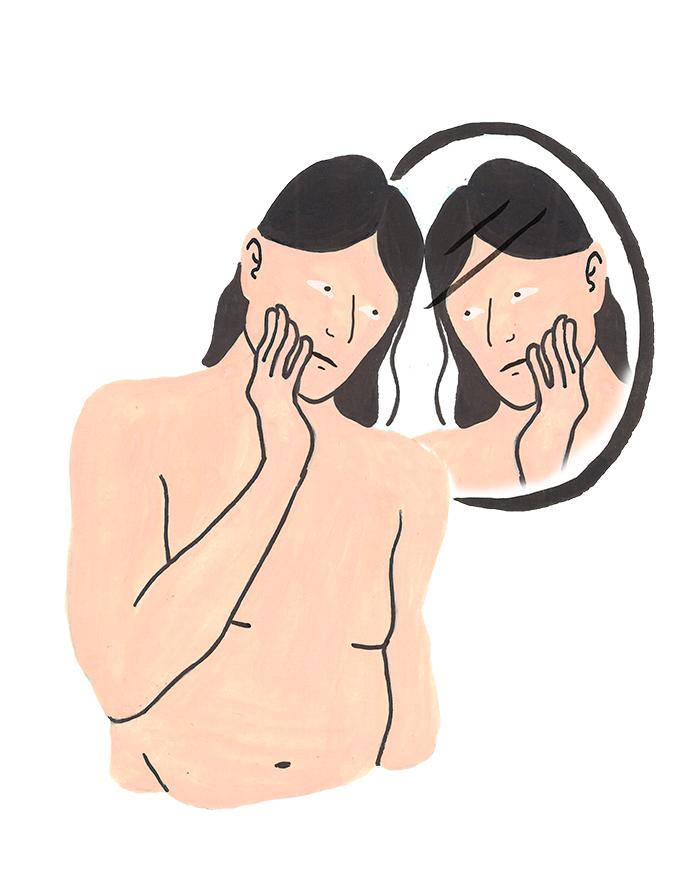 Person som noga tittar på sitt ansikte i en spegel